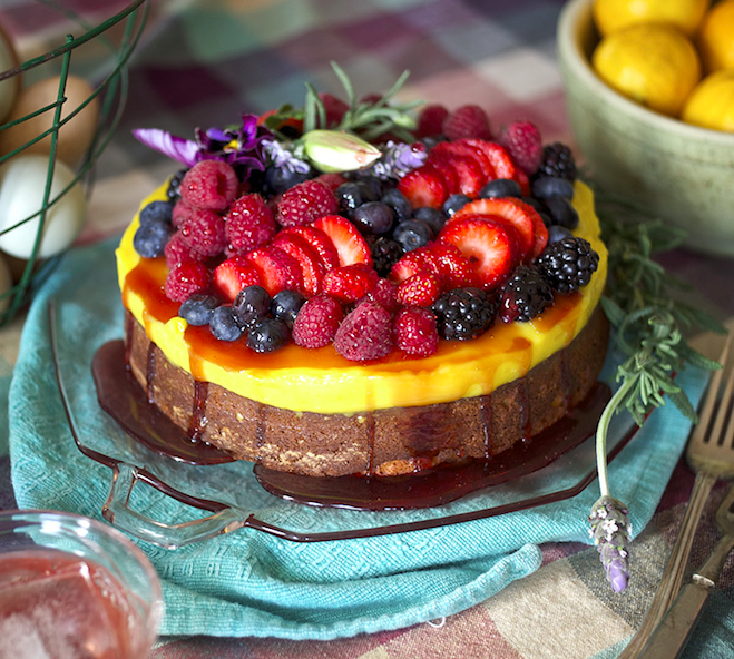 cake with yellow frosting and tons of berries on top