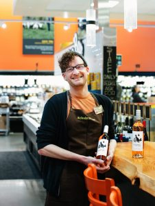 New Seasons Market grocery store employee holding a bottle of local wine