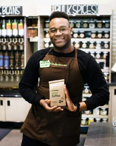 New Seasons Market grocery store employee in the bulk section showing off New Seasons Partner Brand coffee, roasted locally in Portland, Oregon