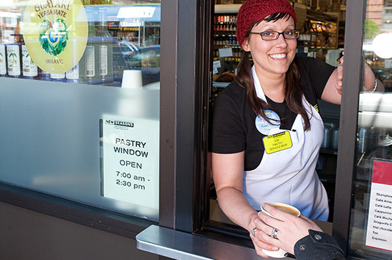 an employee handing a warm beverage out a new seasons drive through window