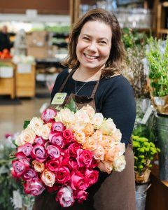 Long-stem fair trade roses held by one of the floral managers at New Seasons Market, Sara