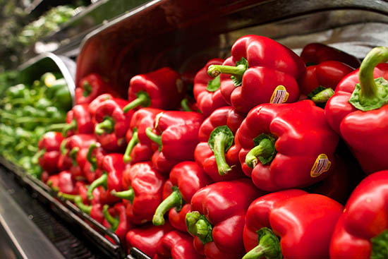 red bell peppers piled high in a new seasons produce department