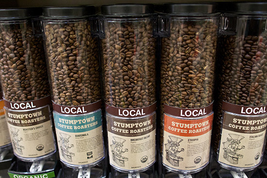 a row of large bulk dispensers of stumptown brand whole coffee beans