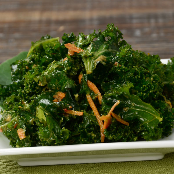 Plate of kale and carrot salad on a wood surface