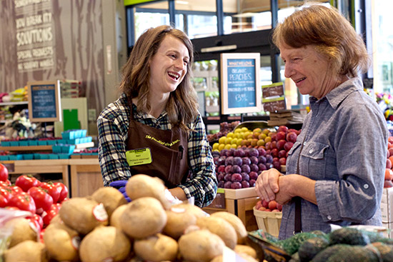 an employee helping a shopper in the produce department