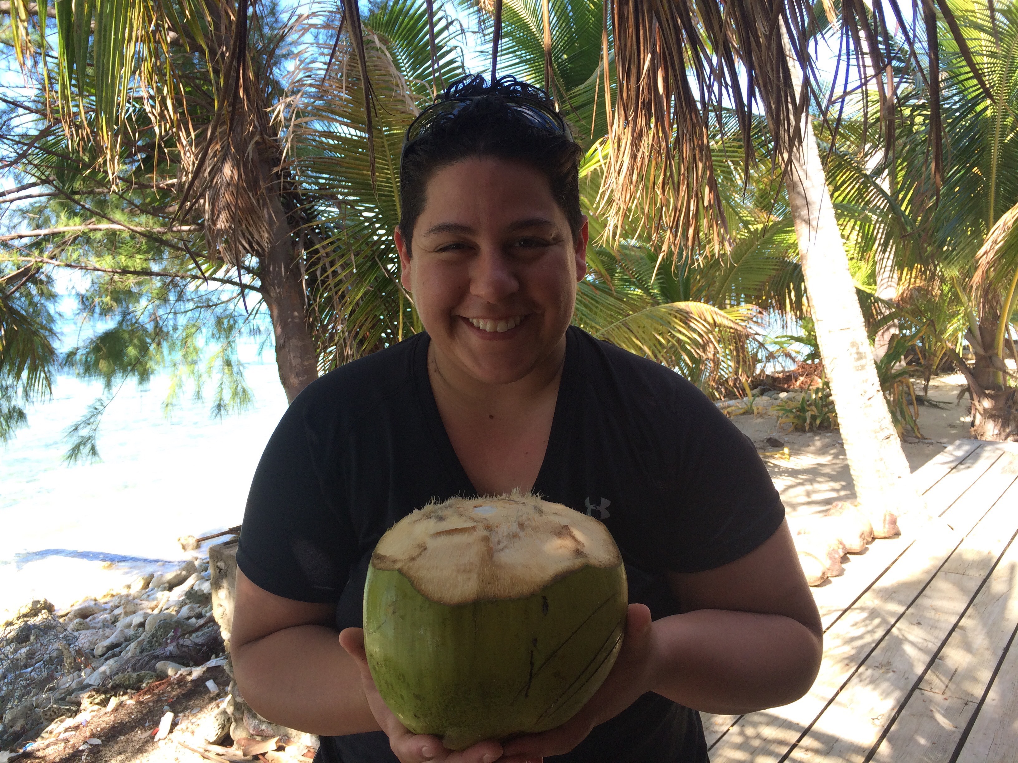 Woman with sunglasses holding a tropical coconut