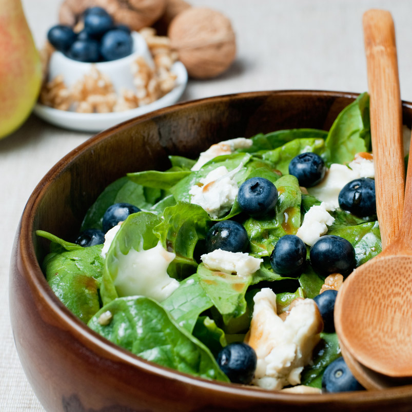 green salad in a wood bowl with blueberries and chicken