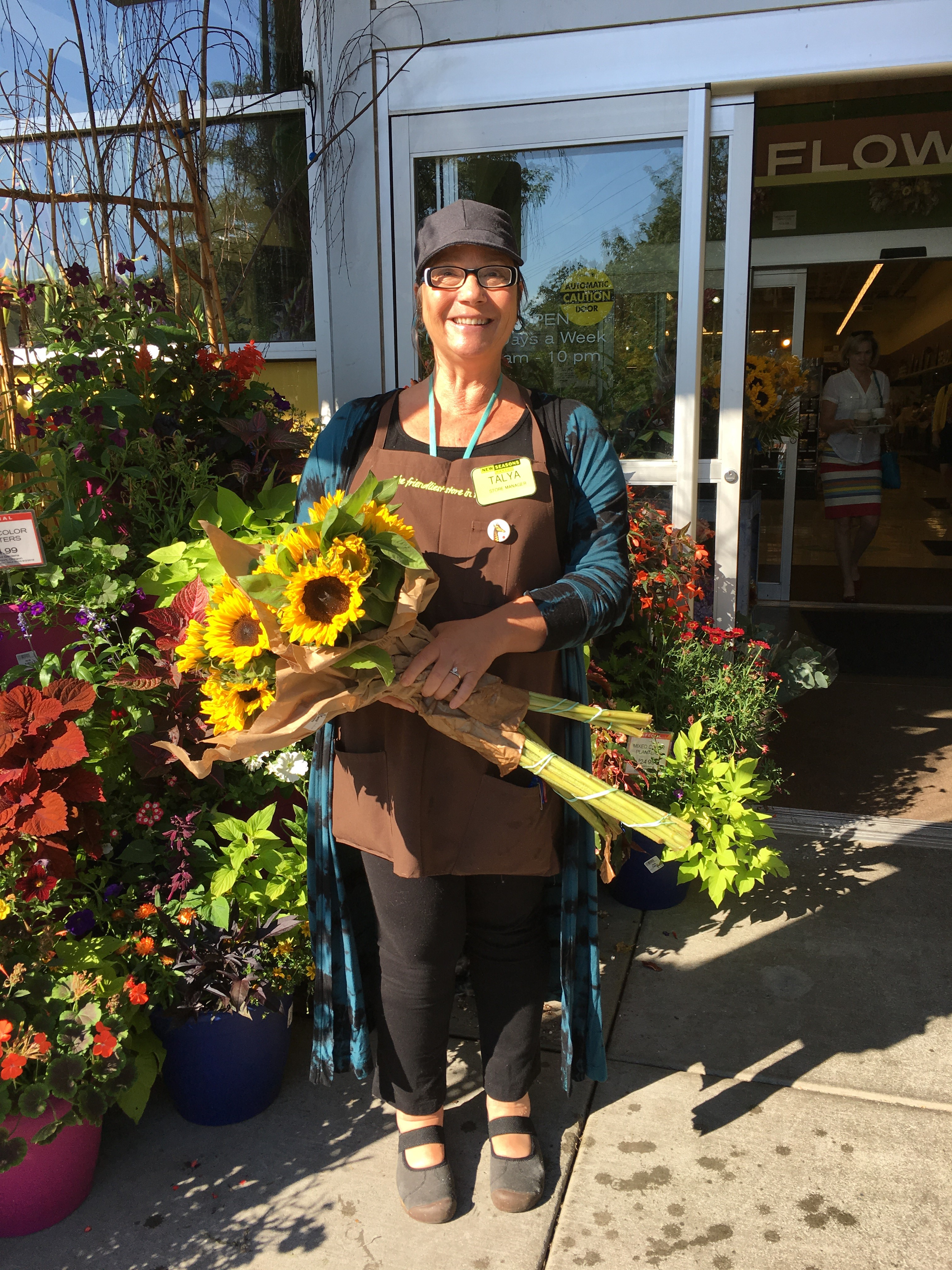new seasons employee holding a bunch of yellow sunflowers by store entrance