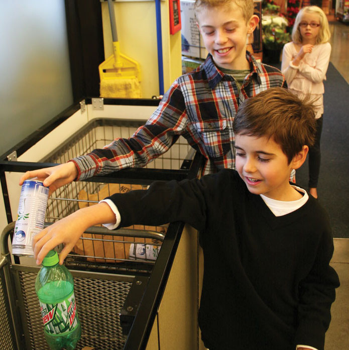 children recycling empty bottles and cans with New Seasons Market Cans for Kids program at each grocery store