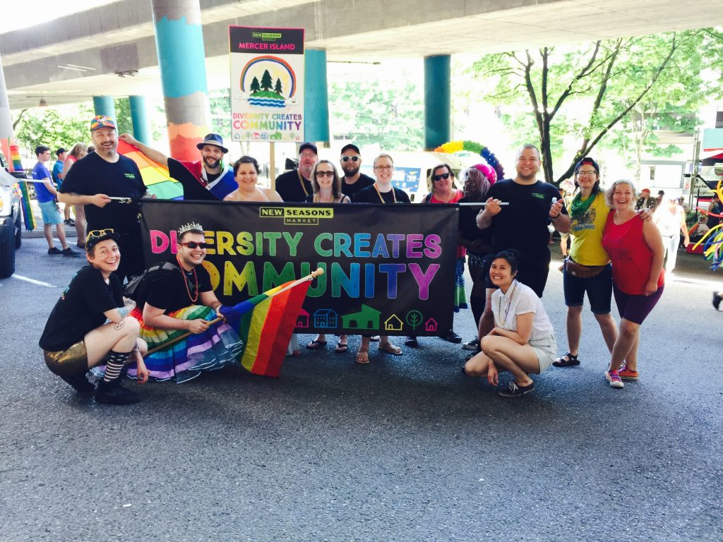 group of people holding new seasons banner reading diversity creates community