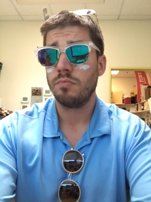 Man looking at the camera with blue shirt and cool shades