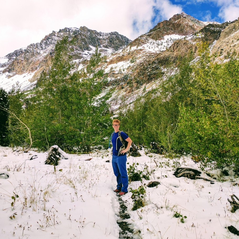 Amy Wolfe standing on a trail in snow with mountains behind