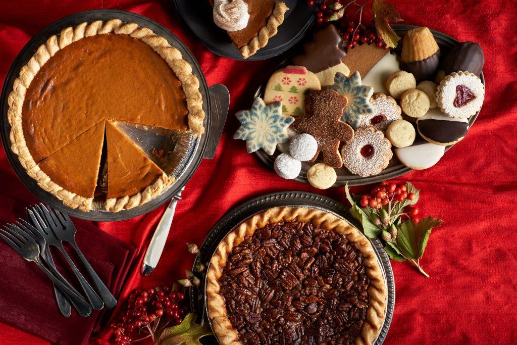 dessert spread with pumpkin pie, pecan pie, and assorted cookies